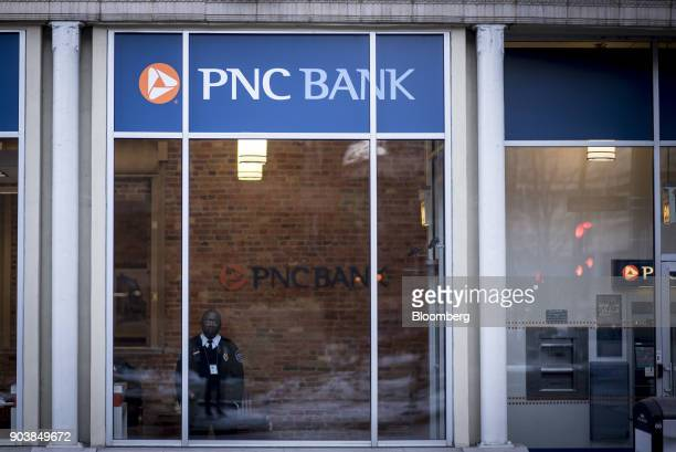 A security guard looks out the window of a PNC Financial Services Group Inc bank branch in downtown Chicago Illinois US on Monday Jan 8 2018 PNC...