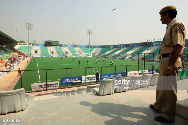 A security guard looks over the view of the virtually empty stadium at the hockey preliminary round match between Pakistan and Scotland during Day...