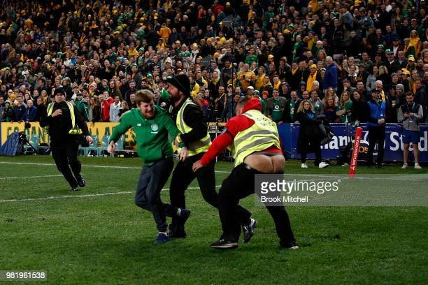 A security guard loses his pants as he chases down a pitch invader after the Third International Test match between the Australian Wallabies and...