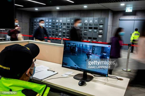 A security guard monitors a temperature checkpoint as people arrive at the entrance to a government office building in Hong Kong on March 2 2020 Hong...