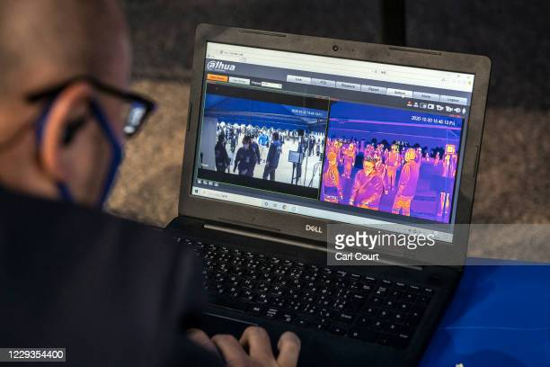 Security guard monitors a thermal imaging camera as fans arrive at Yokohama Stadium ahead of a baseball match between Yokohama DeNA Baystars and...