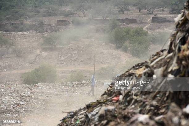Security guard near a mountain formed by garbage at a landfill site ahead of the World Environment Day, at Okhla on June 4, 2018 in New Delhi, India....