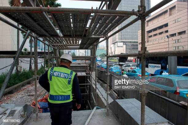 A security guard of Jakarta's MRT construction project stands guard at the entrance of the tunnel in Jakarta on June 7 2018 as the right side shows...