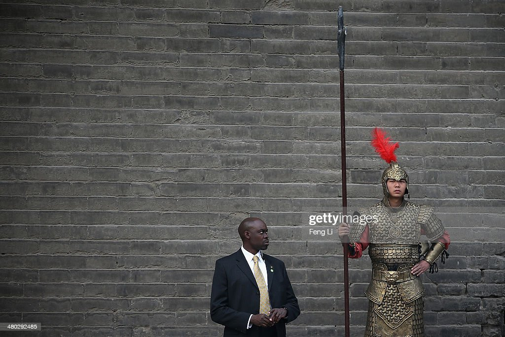 XI'AN, CHINA - MARCH 24: A security guard of U.S. first lady Michelle Obama stands beside a man wearing a Chinese ancient warrior costume during Obama's visit at the City Wall on March 24, 2014 in Xi'an, China. Michelle Obama's one-week-long visit in China will be focused on educational and cultural exchanges.