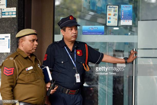 Security guard of Yes Bank and police personnel stand guard outside the branch office at Janpath, in New Delhi, India, on Friday, March 6, 2020.