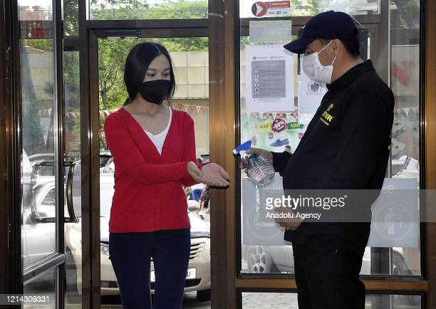 Security guard offers hand sanitizer to a woman at the entrance of a shopping center after malls reopened within the easing coronavirus pandemic...