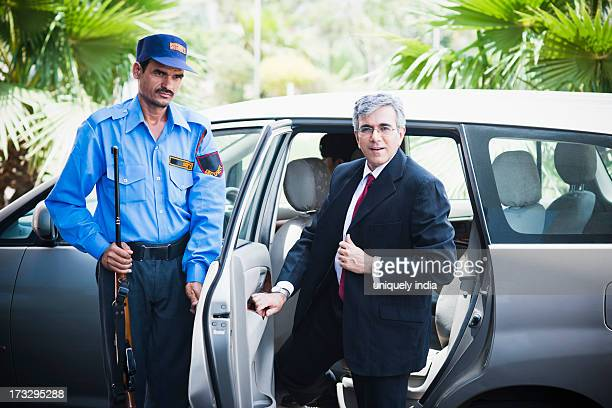 Security guard opening car door for a businessman
