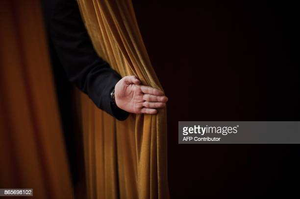 Security guard opens a curtain during the closing session of the 19th Communist Party Congress in Beijing on October 24, 2017. Chinese President Xi...