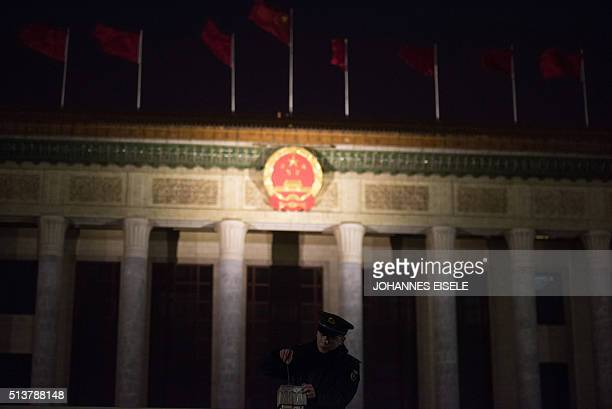 A security guard opens a gate outside the Great Hall of the People in Beijing before the opening ceremony of the National People's Congress on March...
