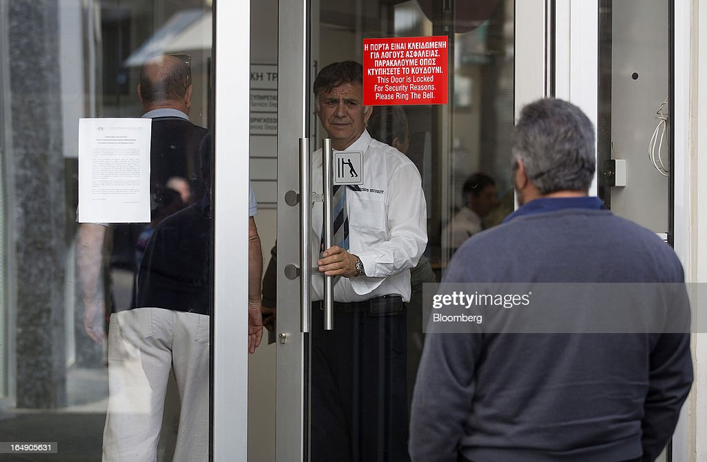 A security guard opens the door to a customer, limiting the number of people inside a branch of a Cyprus Popular Bank Pcl, also known as Laiki Bank, as other customers wait outside in Nicosia, Cyprus, on Friday, March 29, 2013. Cypriots face a second day of bank controls over their use of the euro as officials in Europe urged the country to move quickly to lift the restrictions, the first time they have been imposed on the common currency. Photographer: Simon Dawson/Bloomberg via Getty Images