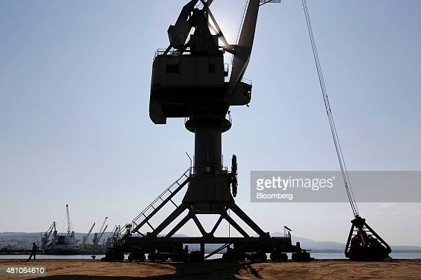 A security guard patrols at the base of a shipping crane on the dockside at Thessaloniki port operated by Thessaloniki Port Authority SA in...