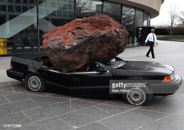 A security guard patrols the plaza near a crushed car sculpture at the Smithsonian Hirshhorn Museum and Sculpture Garden that is closed due to a...