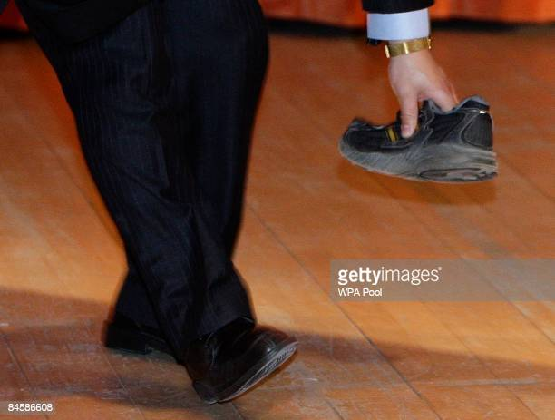 A security guard picks up a shoe that was thrown towards Chinese Premier Wen Jiabao as he delivered a speech at the University of Cambridge on...