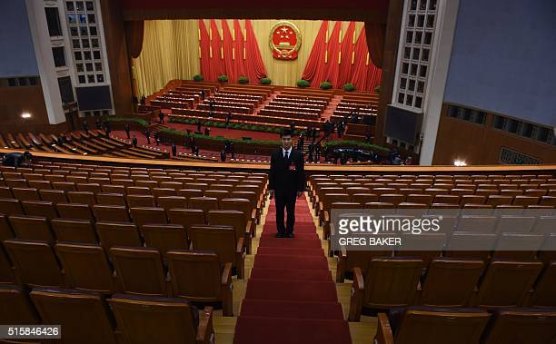 A security guard prepares to check seats after the closing session of the National People's Congress in the Great Hall of the People in Beijing on...