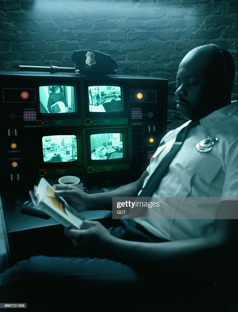 security guard readingsurveillance monitors in background stock