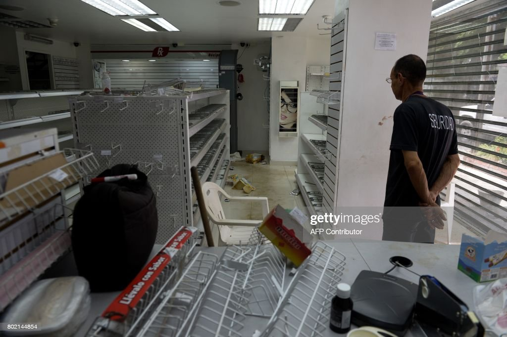 A security guard remains inside a looted pharmacy in Maracay, Aragua state, Venezuela on June 27, 2017. /