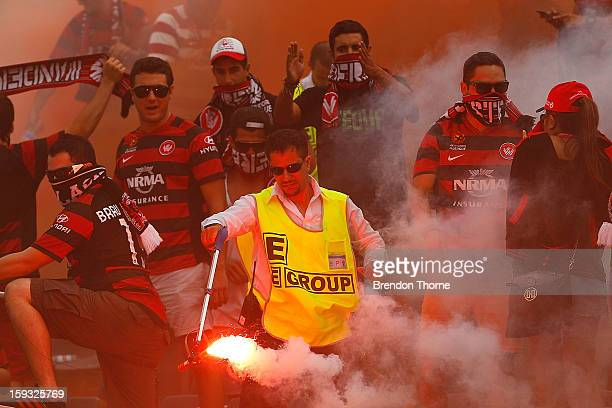 A security guard removes a flare from Wanderers supporters during the round 12 WLeague match between the Western Sydney Wanderers and Sydney FC at...