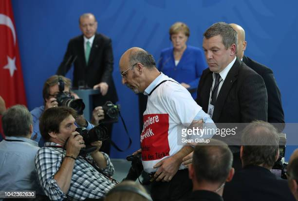 A security guard removes journalist Yirgit Ertugral after he sat in the front row wearing a tshirt that reads Freedom of the press for journalists in...