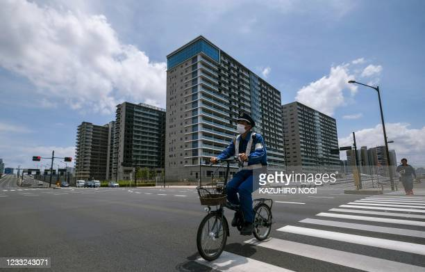 Security guard rides a bicycle across a street near the Olympic and Paralympic athletes' village in Tokyo on June 3 50 days before the opening...