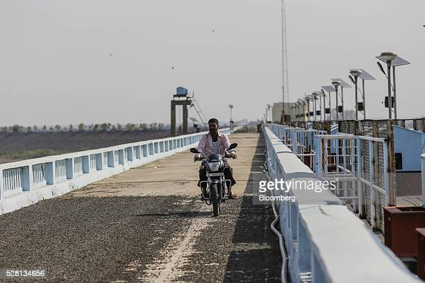 A security guard rides a motorcycle along the crest of Manjara Dam near Latur Maharashtra India on Saturday April 16 2016 Hundreds of millions of...