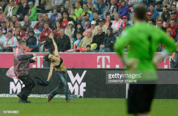 A security guard runs after a female streaker who crosses the pitch during the German first division Bundesliga football match FC Bayern Munich vs SC...