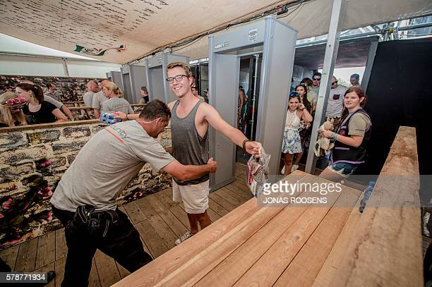 A security guard searches people at the entrance of the 12th edition of the Tomorrowland electronic music festival on July 22 2016 at the De Schorre...