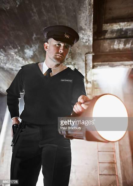 Security guard shining flashlight into bunker