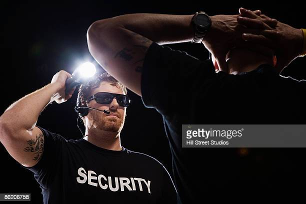 security guard shining flashlight on man - bouncer security staff stock photos and pictures