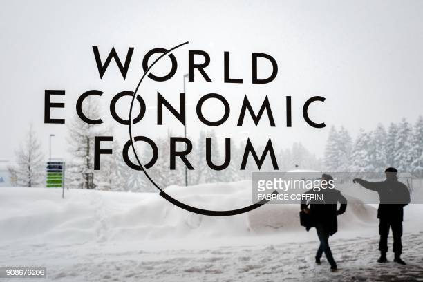 TOPSHOT A security guard show the way to a man outside of the Davos Congress Centre under snow ahead of the opening of the World Economic Forum 2018...