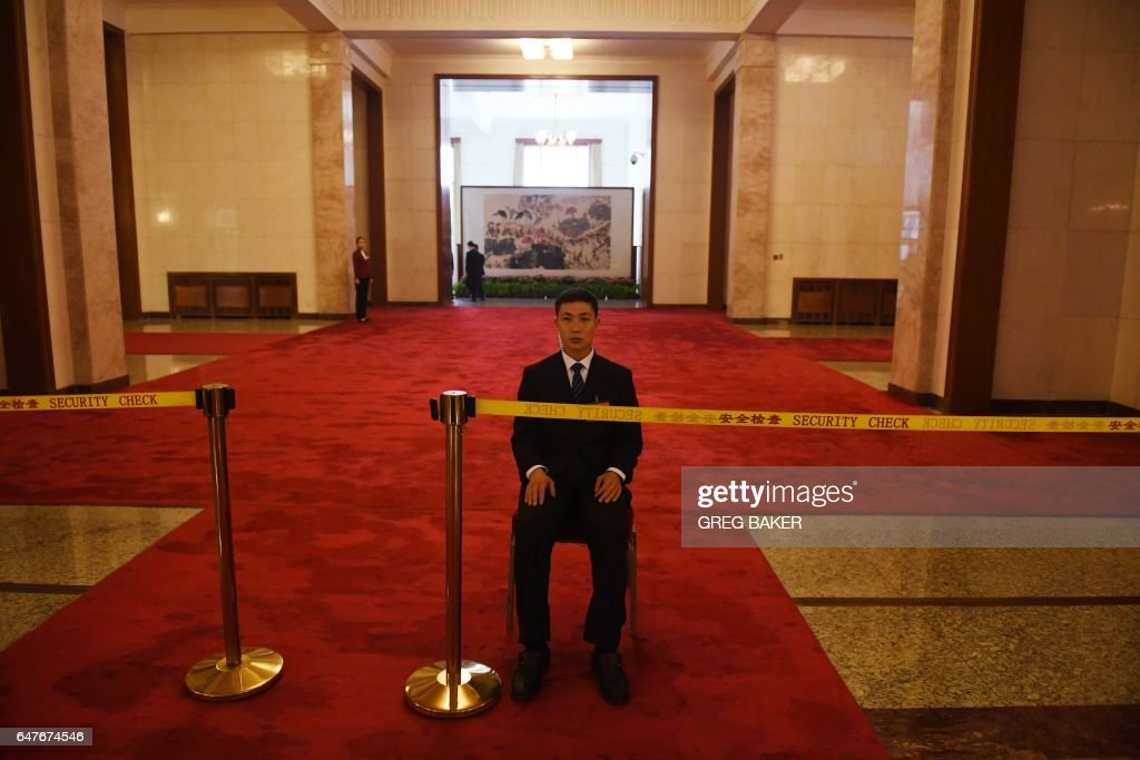 TOPSHOT - A security guard sits at an entrance during a National People's Congress press conference at the Great Hall of the People in Beijing on March 4, 2017. China will raise defence spending by 'around seven percent' this year as it guards against 'outside meddling' in its disputed territorial claims in Asian waters, a top official said on March 4, 2017. /