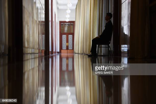 TOPSHOT A security guard sits in a corridor leading to the Hong Kong Hall during the National People's Congress at the Great Hall of the People in...
