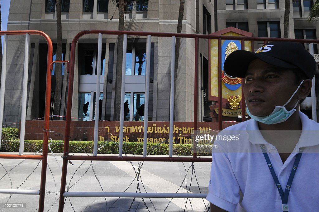 A security guard sits in front of smashed windows at the Stock Exchange of Thailand (SET) building in Bangkok, Thailand, on Friday, May 21, 2010. Thailand's stock exchange can open for trading at a backup site even though the main building was damaged in a fire during unrest, President Patareeya Benjapolchai said today. Photographer: Udo Weitz/Bloomberg via Getty Images