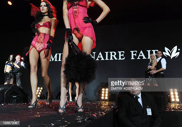 A security guard sits near a podium as models present a collection of underwear during Moscow Millionaire Fair 2010 on October 22 2010 AFP PHOTO /...