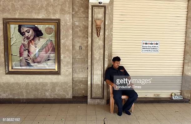 A security guard sits outside a closed jeweler shop on the strike day at Borivali on March 3 2016 in Mumbai India Jewellers started their threeday...