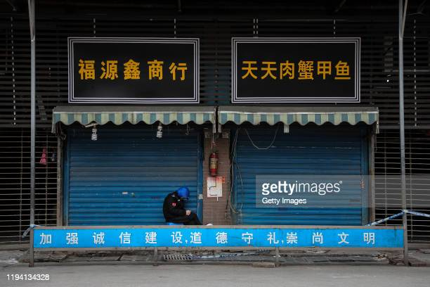 A security guard sits outside the closed Huanan Seafood Wholesale Market which has been linked to cases of Coronavirus on January 17 2020 in Wuhan...