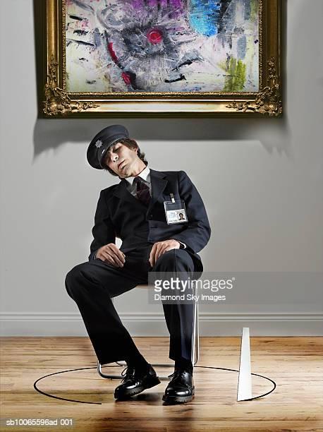 security guard sleeping in chair, saw cutting wooden floor around it - defending stockfoto's en -beelden