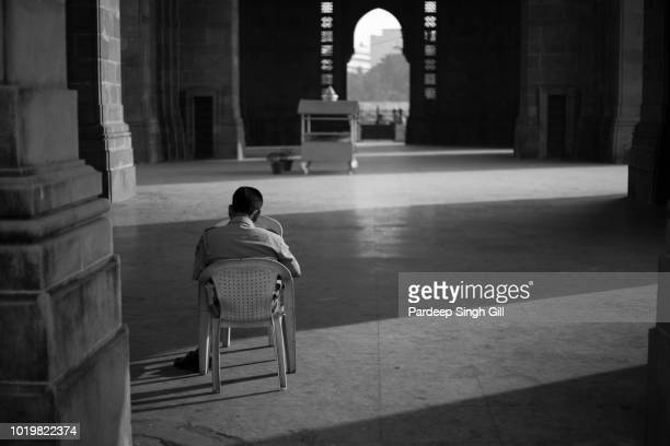A security guard sleeps in the hall of the Gateway of India in Mumbai, India.