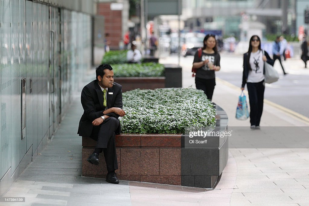 A security guard smokes a cigarette during a break in the financial district of Canary Wharf on June 28, 2012 in London, England.