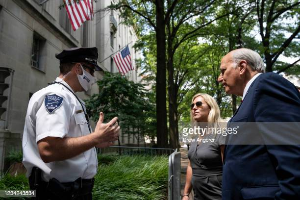 Security guard speaks to Rep. Marjorie Taylor Greene and Rep. Louie Gohmert as they try to gain entry to the U.S. Department of Justice on July 27,...