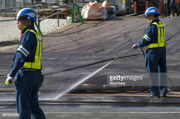 A security guard sprays water near an entrance gate to the construction site of the New National Stadium a venue for 2020 Summer Olympics and...