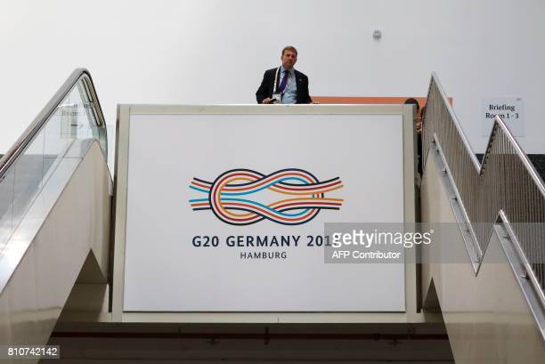 A security guard stand above a G20 logo on the second day of the G20 meeting in Hamburg northern Germany on July 8 2017 The G20 summit wraps up with...