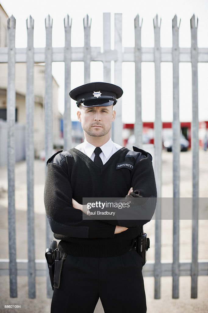 Security guard standing in front of gate : Stock Photo