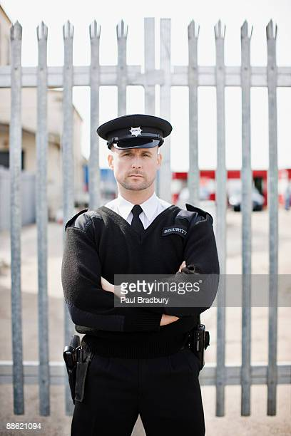 security guard standing in front of gate - guarding stock photos and pictures