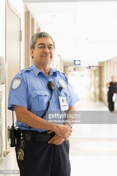 security guard standing in hospital corridor - watchmen stock pictures, royalty-free photos & images