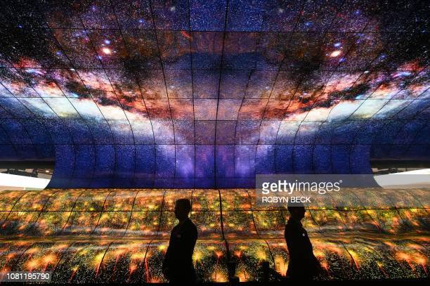 A security guard standing in the Massive Curve of Nature display of 250 curved LG OLED televisions is reflected in a mirror on the last day of CES...