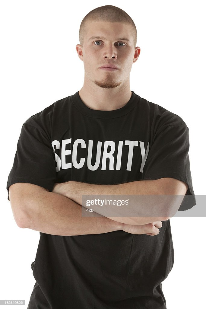 Security guard standing with his arms crossed : Stock Photo