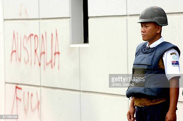 A security guard stands alert next to a graffiti on the wall of the Australian embassy in Jakarta 27 March 2006 Australia's envoy to Jakarta Bill...