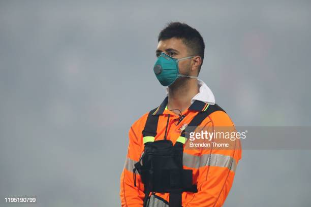 A security guard stands amongst smoke haze during the Big Bash League match between the Sydney Thunder and the Adelaide Strikers at Manuka Oval on...