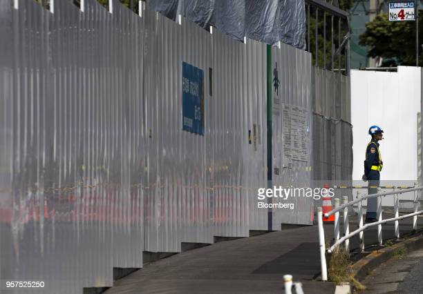A security guard stands at an entrance gate to the construction site of the New National Stadium a venue for 2020 Summer Olympics and Paralympics in...