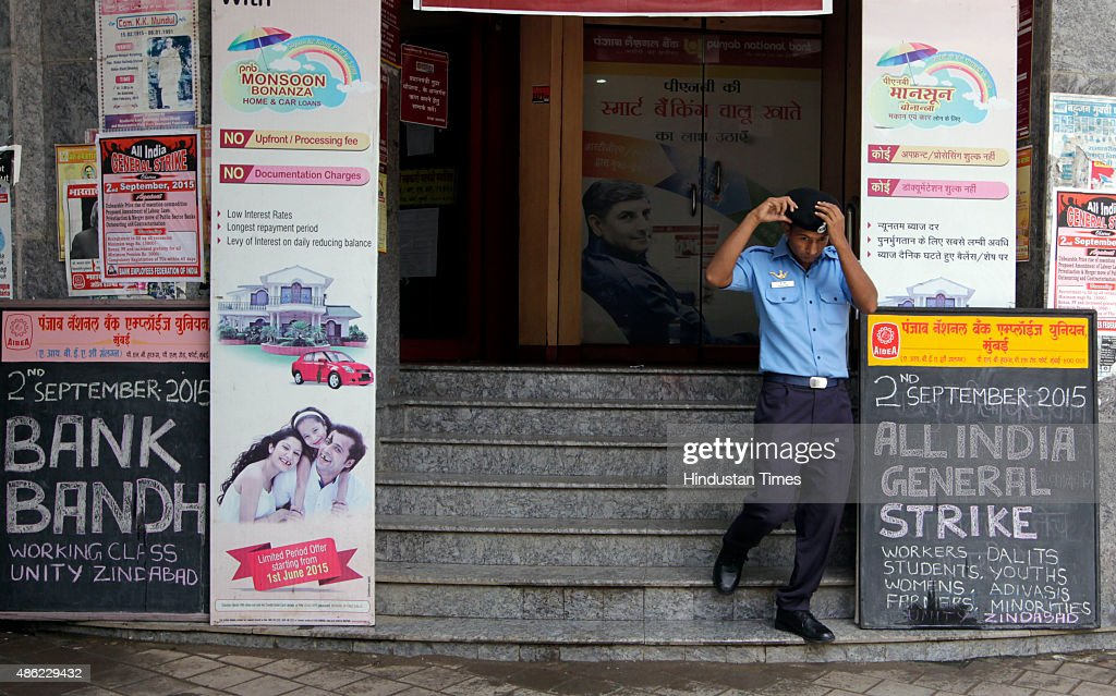 A security guard stands at gate as strike notice written on board outside the branch of Punjab National Bank during a oneday strike at Fort on...